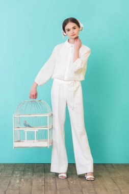 beautiful girl in white outfit with parrot in cage, on turquoise