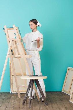 teen artist painting on easel in workshop