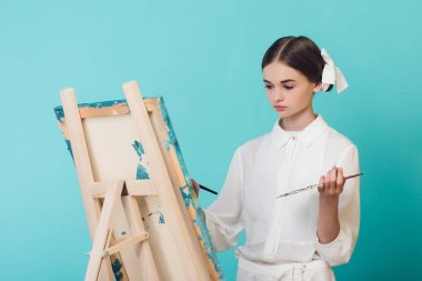 beautiful girl painting on easel with brush and palette, isolated on turquoise