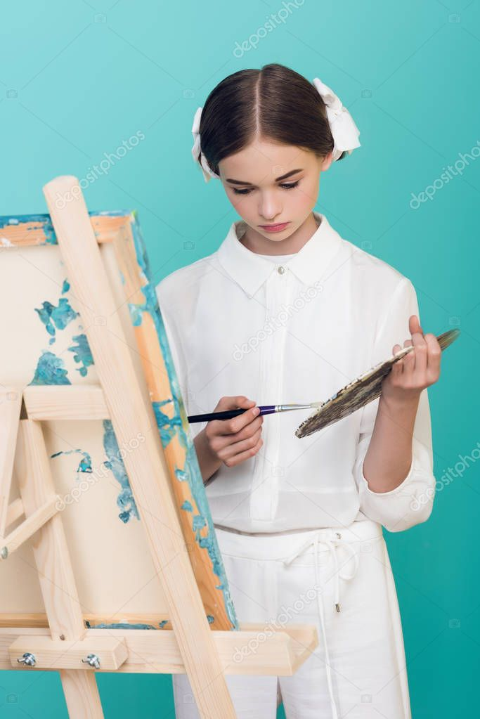 elegant teen artist painting on easel with brush and palette, isolated on turquoise