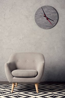 armchair, carpet and clock on wall in simple grey room