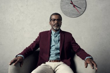 confident middle aged african american man sitting in armchair with clock on wall