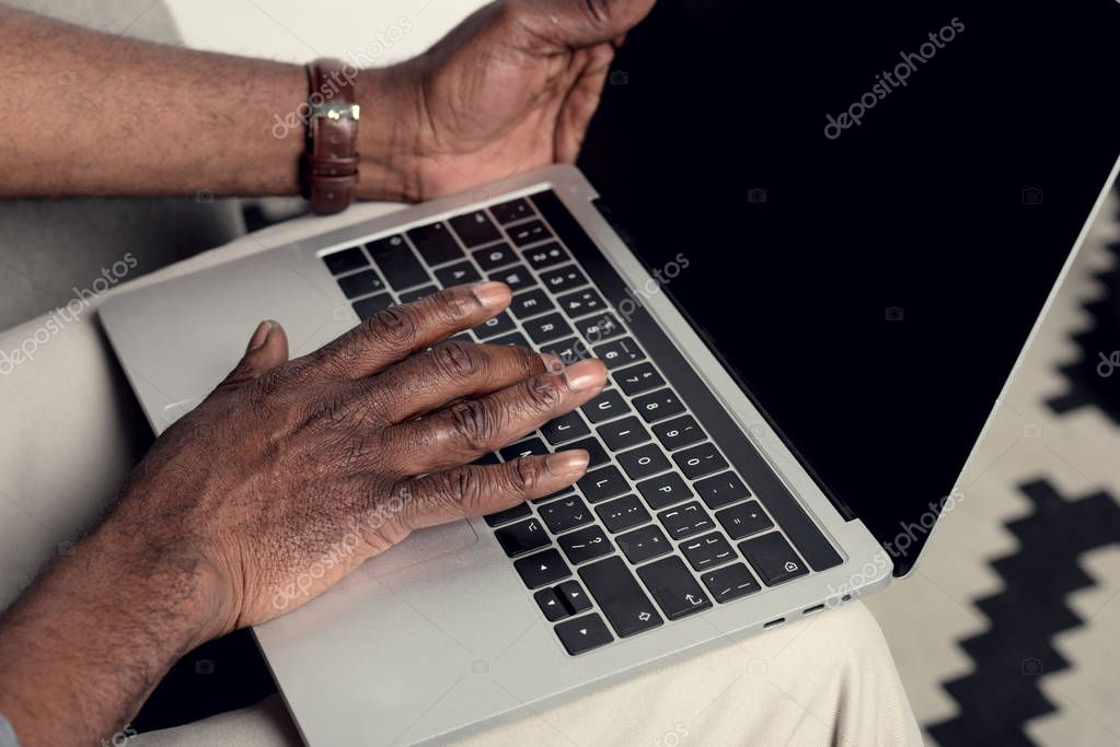 Partial view of african american man typing on laptop with blank screen
