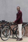Stylový americký podnikatel s kolo na parkování pro jízdní kola