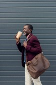 Fotografie fashionable african american man with leather bag and disposable cup of coffee