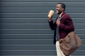 Fotografie stylish african american man with leather bag and coffee to go