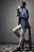 Fotografie reifer afroamerikanische Mann Kaffee zu trinken und auf Hocker sitzend