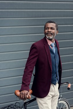 stylish mature african american man in burgundy jacket posing near bicycle