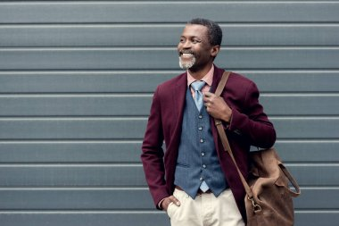 happy stylish african american man in burgundy jacket with leather bag