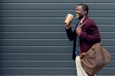 stylish african american man with leather bag and coffee to go