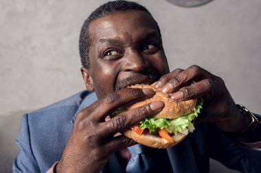 hungry african american businessman eating hamburger