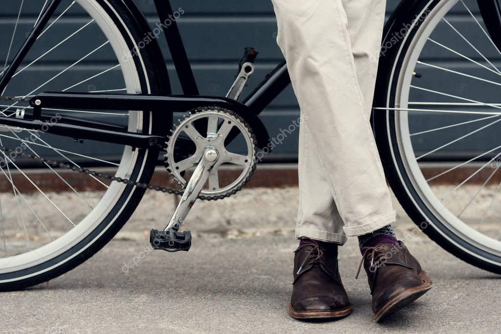 partial view of man in white pants posing near bike