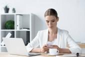 Fotografie krásná mladá podnikatelka pomocí smartphone v kanceláři