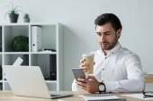 Fotografie hübscher junger Geschäftsmann mit Pappbecher Kaffee mit Smartphone am Arbeitsplatz