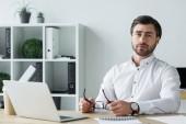 pohledný mladý podnikatel drží brýle sedí na pracovišti a při pohledu na fotoaparát
