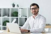 boldog fiatal üzletember modern irodában dolgozik laptop és látszó-on fényképezőgép