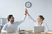 šťastné úspěšné manažery pracující s notebooky spolu v kanceláři a dávat vysoké pět