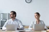 Fotografie mladí manažeři pracují s notebooky spolu v kanceláři a hledat dál