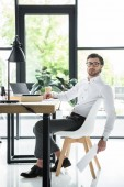 side view of handsome young businessman sitting at modern workplace in office and looking at camera