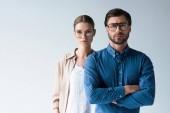 vážný muž a žena ve stylovém oblečení a brýle izolované na bílém