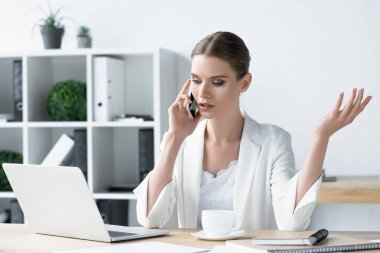 confident young businesswoman talking by phone at office