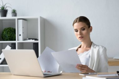 focused young businesswoman doing paperwork at office