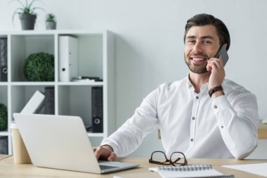 smiling young businessman talking by phone at workplace and looking at camera