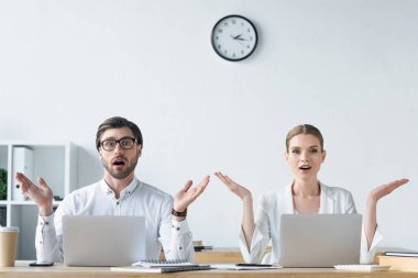 surprised young managers raising hands while working with laptops together at office