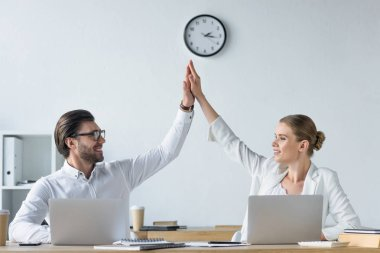 happy successful managers working with laptops together at office and giving high five