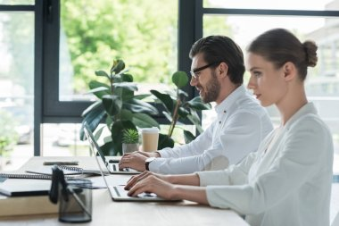 side view of business partners working with laptops together at office