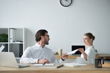 happy businesspeople passing documents at workplace in office