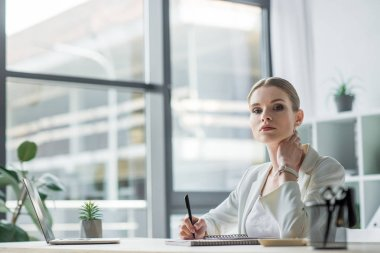 beautiful young businesswoman sitting at workplace in modern office and looking at camera
