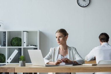 businesswoman sitting at workplace and looking away while his colleague working on background