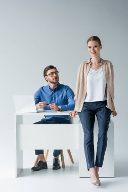 young businessman sitting at workplace while his colleague sitting on his desk on white