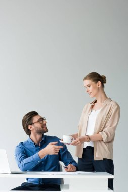 smiling attractive secretary passing cup of coffee to boss isolated on white