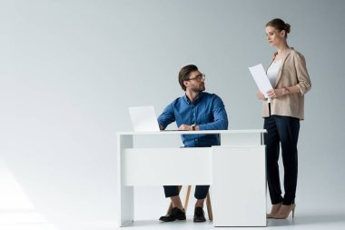 businessman sitting at workplace while his colleague standing with documents behind him on white