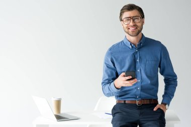 handsome young businessman with smartphone leaning back at workplace isolated on white