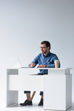 handsome young businessman using laptop at workplace on white