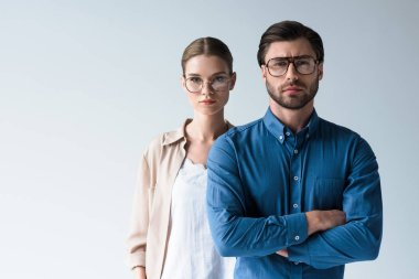 serious man and woman in stylish clothing and eyeglasses isolated on white