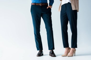 cropped shot of man and woman in stylish pants and shoes on white