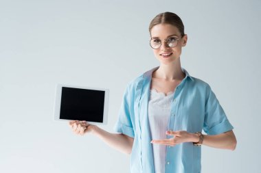 happy young woman showing tablet with blank screen isolated on grey
