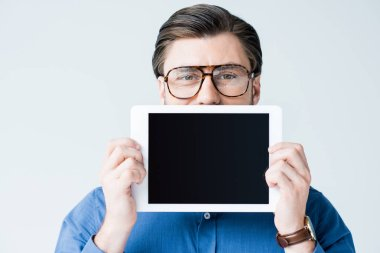 young man covering half of face with tablet with blank screen isolated on white