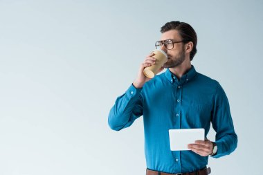 attractive young man with paper cup of coffee and tablet isolated on white