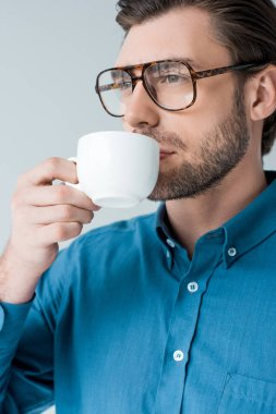 close-up portrait of young man drinking coffee from cup isolated on white