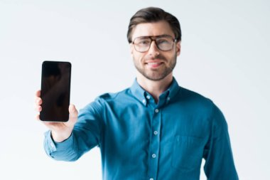 smiling young man holding smartphone with blank screen isolated on white
