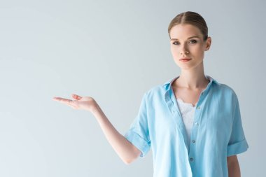 beautiful young woman in blue shirt pointing at blank space isolated on grey