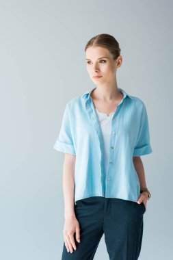 beautiful young woman in stylish blue shirt isolated on grey