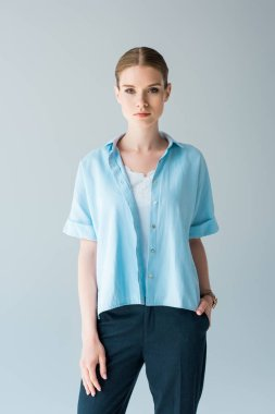 beautiful young woman in stylish blue shirt looking at cameraisolated on grey
