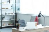 laptop a káva s sebou na dřevěný stůl v útulném pokoji s moderním interiérem