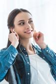 beautiful smiling teenage girl listening music in earphones and looking away
